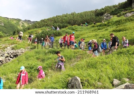 TATRA MOUNTAINS, POLAND - AUGUST 9, 2014: Tourists hike in Tatra Mountains, Poland. Tatra National Park was visited by 2.7 million people in 2013.