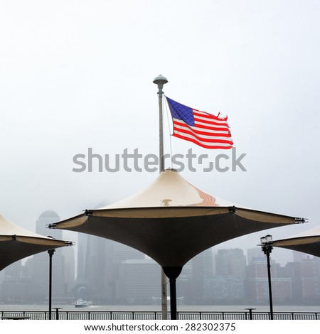 Tattered American flag blowing in the wind with Manhattan skyline on background on a rainy day - stock photo