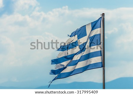 Tattered Greek flag waving in the clouds on the blue sky background. concept for failure, debit, unique currency and financial bond - stock photo