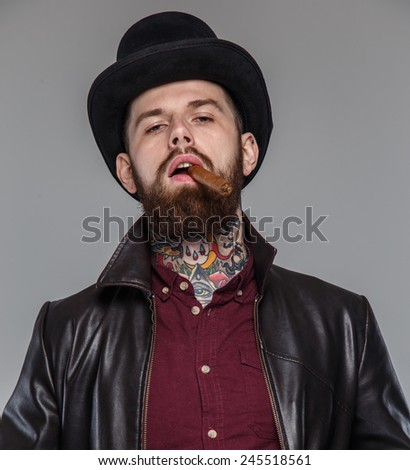 Tattoed male with cigar in his mouth - stock photo