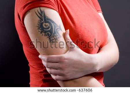 Tattoo at the woman on a forearm - stock photo