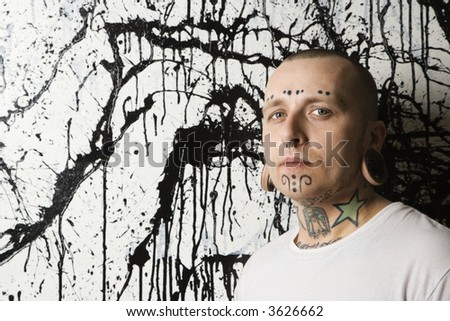 Tattooed and pierced man against paint splattered background.