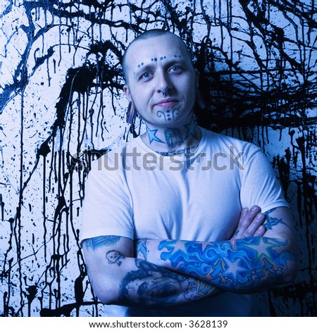 Tattooed and pierced man standing against paint splattered background.