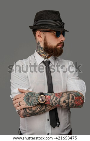Tattooed bearded man in white shirt isolated on grey background. - stock photo