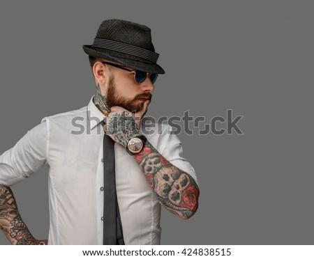 Tattooed bearded man in white shirt isolated on grey background. - stock photo