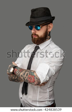Tattooed bearded man in white shirt isolated on grey background.