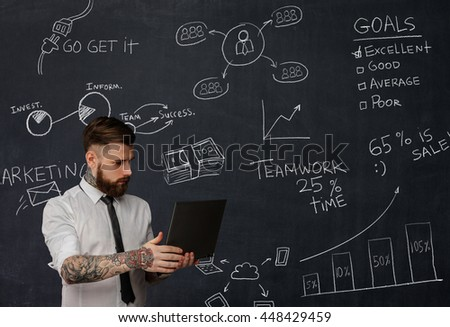 Tattooed bearded teacher with laptop over school desk with formulas.