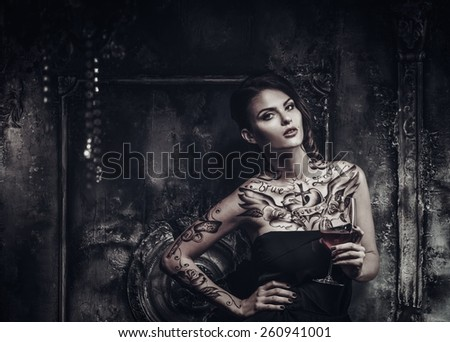 Tattooed beautiful woman in old spooky interior - stock photo