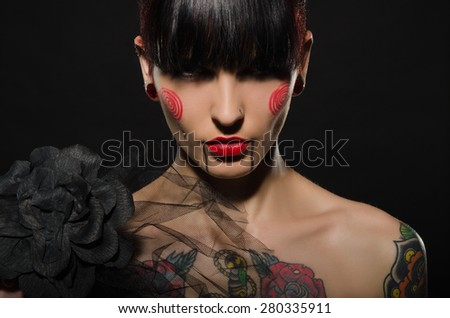tattooed charming brunette with black flower on dark background - stock photo