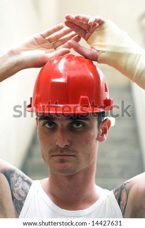 tattooed man with red helmet and hand in plaster - stock photo
