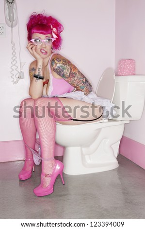 Tattooed woman sitting on toilet seat with her panties down - stock photo