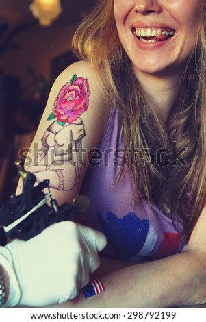 tattooer showing process of making a tattoo on young beautiful hipster woman with blonde  hair arm. Tattoo design in the form pin-up girl with flower head. Vintage picture - stock photo