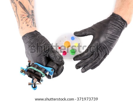 Tattooist hands in black gloves with tattoo machine and colourful inks isolated on white background, close up - stock photo