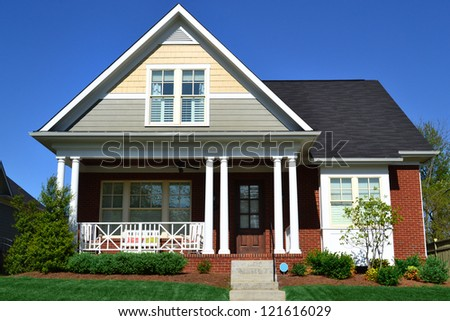Taupe, Yellow, and Brick Cape Cod American Home with Front Porch - stock photo