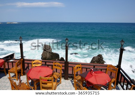 Tavern on sea coast with wooden chairs and tables - stock photo