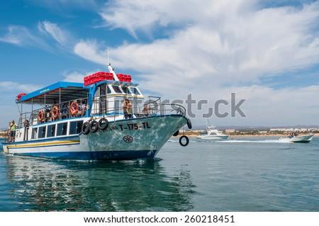 TAVIRA, PORTUGAL - SEPTEMBER 16: passenger boat make short trip to Tavira Island on September 16, 2012 in Tavira, Portugal. The access to Tavira Island is provided by boats from Quatro Aguas peer. - stock photo