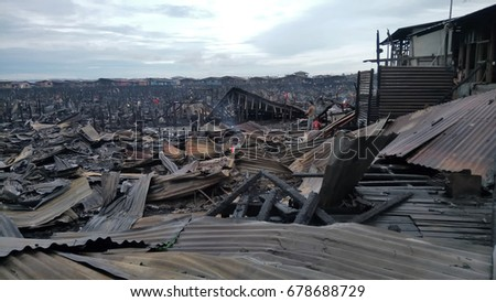 Tawau, Malaysia - July 01, 2017: Squatters living on makeshift houses on stilts at sea at Kampung Hidayat, Batu 4, had their homes destroyed in a blaze.