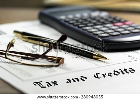 Tax and credits concept. Getting refund from the income tax return. Calculator, glasses and black pen on financial documents in the background.  - stock photo