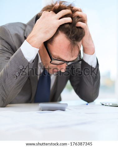 tax, business and stress concept - stressed businessman with papres, laptop and calculator - stock photo