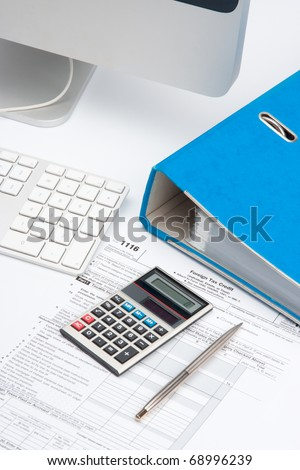 Tax concept - tax form, part of computer, keyboard, calculator, office folder and pen - stock photo