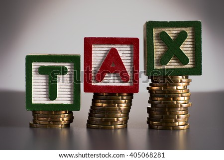 TAX Concept with green and red wooden block on stacked coins show increasing of coins - business and finance concept - stock photo