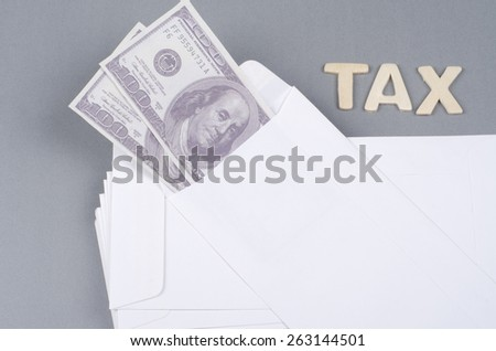Tax concept with text and money in envelope