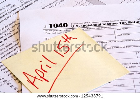 Tax Day Reminder - A 1040 tax form and a reminder note with April 15th written on it. The corner of the note is hiding the date to add to the image usefulness.