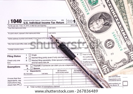 Tax form and Money. Filling the forms and hoping for a tax refund return - stock photo