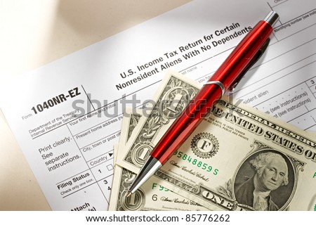 Tax form and pen and dollars