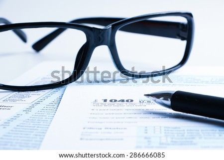 Tax form business financial concept with a pair of black glasses and a pen aside. - stock photo