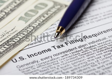 Tax form for nonresident with dollar bills and pen - stock photo