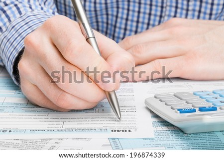 Tax Form 1040 - male filling out tax form - stock photo