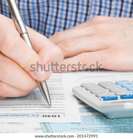 Tax Form 1040 - male filling out tax form - 1 to 1 ratio - stock photo