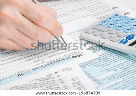 Tax Form 1040 - man filling out tax form - stock photo