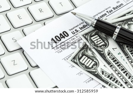 Tax form on keyboard - stock photo