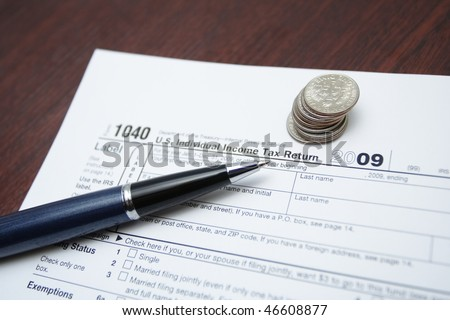 Tax form, pen and coins as a finance concept