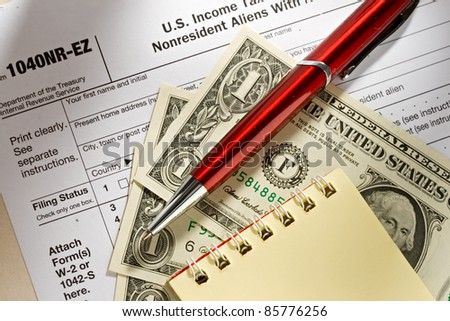Tax form, pen, notepad and dollars - stock photo