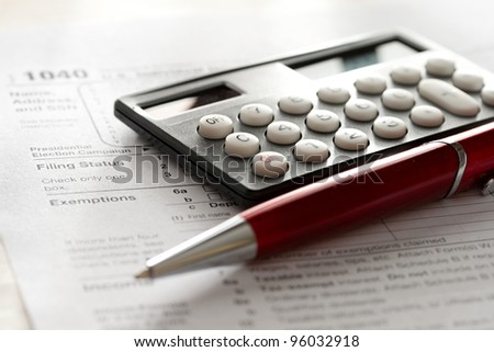 Tax form, red pen and calculator - stock photo