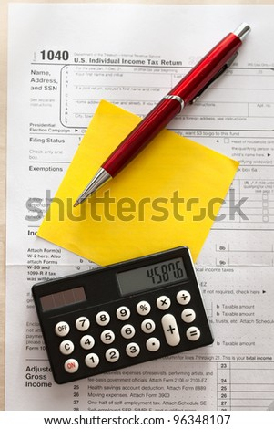 Tax form, red pen, calculator and sticker - stock photo