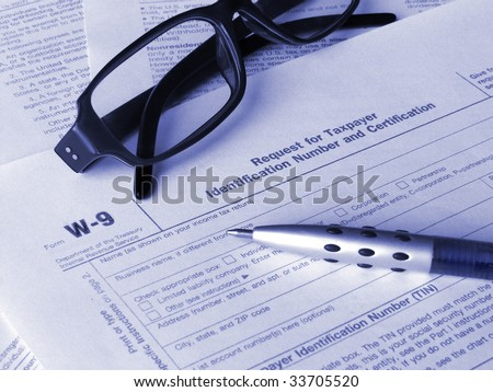 Tax form W-9 glasses and pen. Toned blue. Shallow DOF.