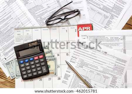 Tax form with calculator and money on the calendar