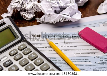 Tax form 1040 with crumpled up forms, calculator, pink eraser and pencil - stock photo