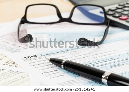 Tax form with glasses, and calculator focus on pen - stock photo