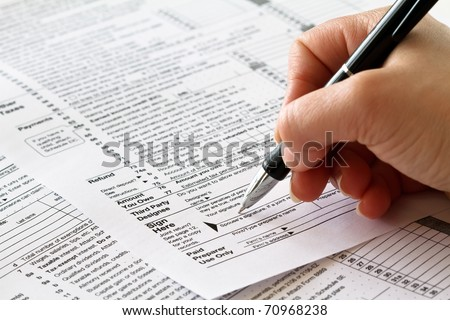 tax form with hand and pen - stock photo