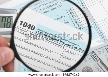 Tax Form 1040 with magnifying glass - stock photo