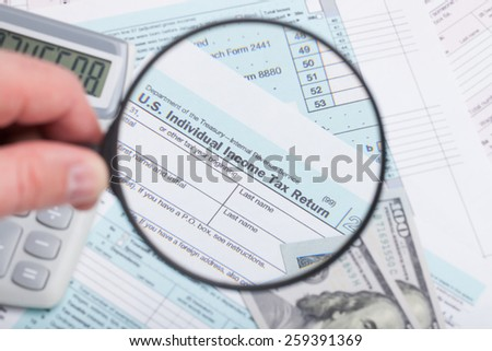 Tax Form with magnifying glass calculator and dollars - stock photo