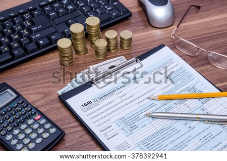tax form with money and copmuter - stock photo