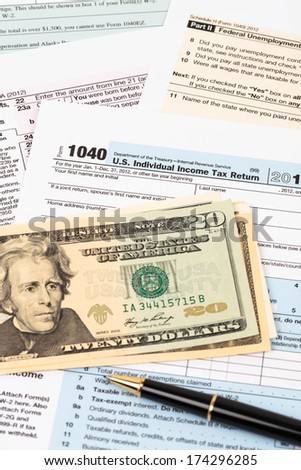 Tax form with pen, and dollar banknote taxation concept - stock photo