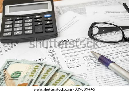Tax form with pen, calculator, glasses and US dollars