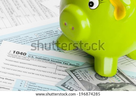 Tax Form 1040 with piggy bank - stock photo